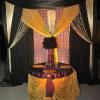 Elaborate colorful backdrop with fancy fabric, crystal chandelier, crystal curtains, cinderella skirt on sweetheart table.